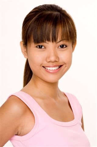 A cute young asian woman in a pink top on white