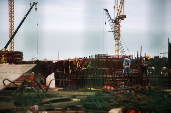 Workers labor as cranes operate at the construction site of Lisboa Palace, developed by SJM Holdings Ltd., in Macau, China, on Sunday, May 10, 2015. Casinos are betting $26.6 billion that if they add hotel rooms and casino tables, they might be able to stop the decline in revenue and start them rising again. Photographer: Lam Yik Fei/Bloomberg