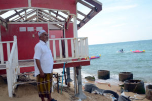 Haad Sai Resort's owner Domea Maha, 63, who built it just three years ago. He has lost two of the his 10 chalets to coastal erosion, including the one behind him, with the sand under its concrete foundation clawed away by the waves.