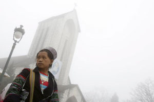 A handicraft vendor waits for customers on a foggy day in front of a Catholic church after Sunday Mass in Vietnam's northwestern resort town of Sapa on Feb 21, 2016.