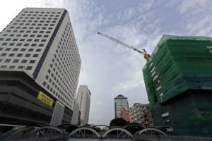 Crane set up at a construction site among tall buildings in downtown Yangon.